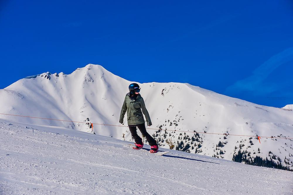 Snowboarder on Sneaky's (ski run),  Aspen/Snowmass ski resort, Snowmass Village, Colorado USA.