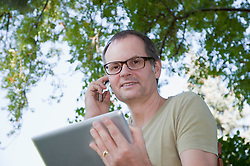 Mature man using digital tablet and cell phone, smiling