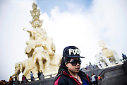 "A Chinese girl wears a baseball cap that reads ""fuck"" on the top of the sacred mountain of Buddhism in Emei Shan, China, August 13, 2014.<br />   <br /> This picture is part of the series ""Urban Chinese Streets"", a journey on the streets of Chinese cities to discover their modern citizens and habits.        <br /> <br /> © Giorgio Perottino"