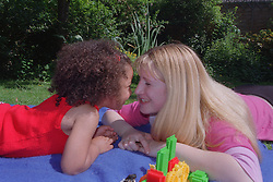 Teenage mother and young daughter lying on picnic blanket in garden smiling at each other,