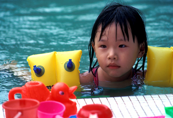 Stock photo of a young Asian girl wearing floaties in a swimming pool