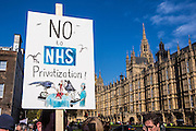 "Placard held up outside the British House of Parliament saying ""No to NHS Privatization"". Protestors have gathered to demonstrate against the government section 75 privatization regulations which they believe will force the National Health Service into privatization."