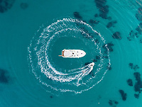 Aerial view of jet ski driving around yacht in the mediterranean sea, Mikonos island, Greece.