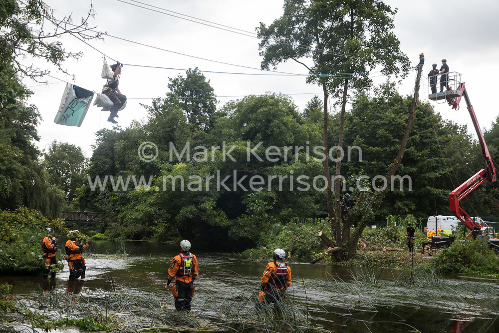 Denham, UK. 24 July, 2020. Swan, an environmental activist from HS2 Rebellion who had been sitting for almost fourteen hours on a line above the shallow river Colne attached to an ancient alder tree which she was trying to protect from destruction during works for the HS2 high-speed rail link, implores police officers standing in a cherry picker not to follow the instructions of a tree surgeon working for the National Eviction Team which had resulted in the hospitalisation of an activist who fell from a line the previous day.