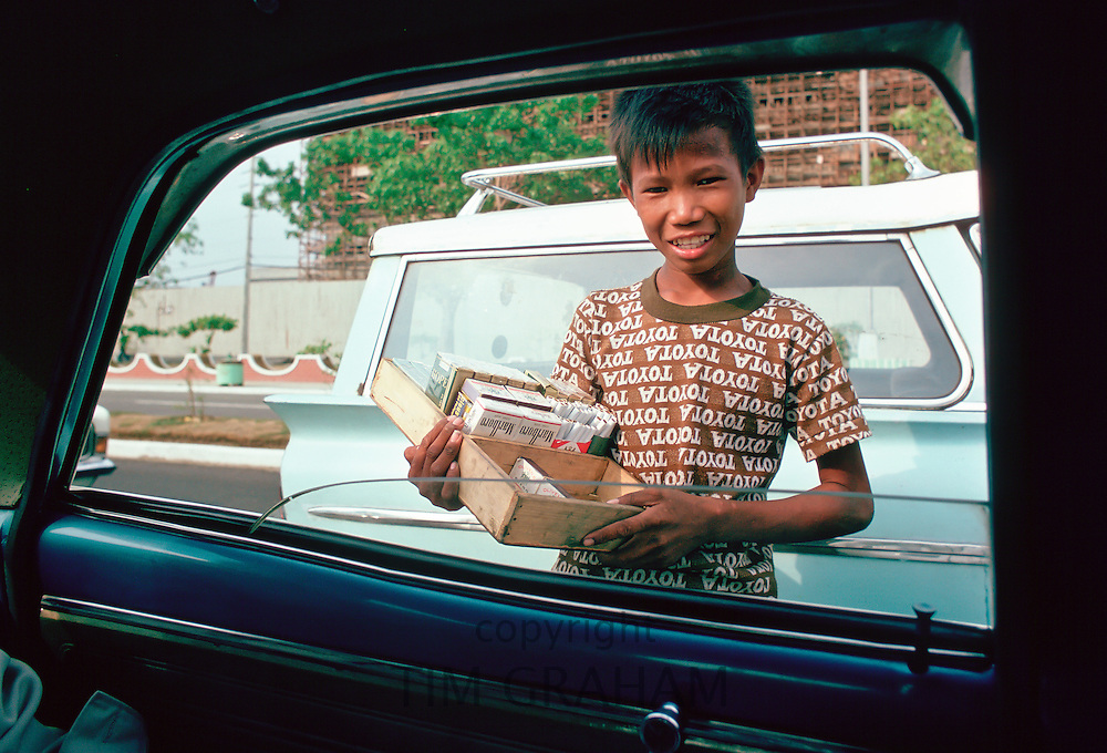 Boy sells cigarettes at car windows in Manila, Philippines
