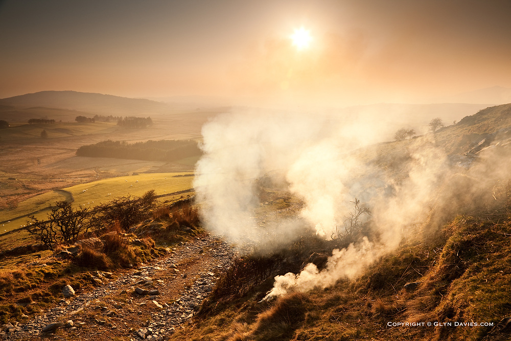 Gorse burning in misty evening sunlight at Cwm Ystradllyn, Snowdonia, North Wales<br /> <br /> As I wandered down off a remote and lonely mountain, I said hello to a farmer on quad bikes who was making his way up the mountainside. I then noticed smoke appearing a little way further down the track. As I rounded the bend I realised he had set fire to gorse bushes, in a controlled burn and was now repeating the process higher up. I was mesmerised by the billowing smoke - crackles of burning twigs the only sound in this silent landscape, and that memory-jogging smell of childhood bonfires in Grandad's garden.