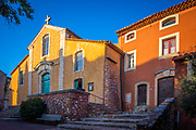 """Roussillon is a commune in the Vaucluse department of the Provence-Alpes-Côte d'Azur region in Southeastern France. In 2016, it had a population of 1,317. Roussillon lies within the borders of the Natural Regional Park of Luberon. In the French natural regional parks system, new economic activities may be developed only if they are sustainable.<br /> <br /> It is noted for its large ochre deposits found in the clay surrounding the village. Ochres are pigments ranging from yellow and orange to red. One of the former ochre quarries can be visited via the """"Sentier des Ocres"""" (Ochre Path), a walk of either 30 or 60 minutes through the old workings."""
