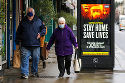 """© Licensed to London News Pictures. 12/01/2021. London, UK. A couple wearing protective face coverings walk past the government's 'Stay Home, Save Lives' Covid-19 publicity campaign poster in north London, as the number of cases of the mutated variant of the SARS-Cov-2 virus continues to spread around the country. The message in the advertising campaign poster says, 'the new variant of COVID-19 is spreading fast' and Prime Minister Boris Johnson has said that the public should """"stay at home"""". Photo credit: Dinendra Haria/LNP"""