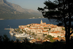Europe, Croatia, Dalmatia, Korcula Island, Korcula town.  View of town and Adriatic Sea, framed by tree silhouette.