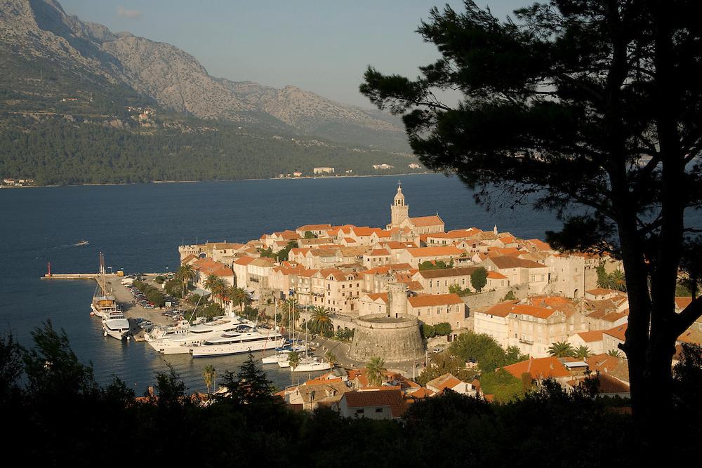 Europe, Croatia, Dalmatia, Korcula Island, Korcula town.  View of town and Adriatic Sea, framed by tree silhouette.
