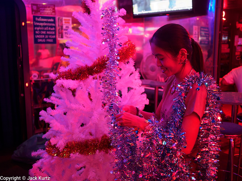 """17 DECEMBER 2013 - BANGKOK, THAILAND:    A worker in a """"go-go"""" bar strings Christmas light on a tree in front of bar on Soi Cowboy in Bangkok.   PHOTO BY JACK KURTZ"""