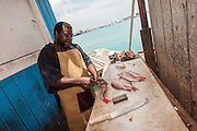 A Bahamian fish monger prepares freshly caught snapper at a roadside food stall at Potter's Cay in Nassau, Bahamas.