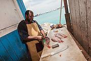 A Bahamian fish monger prepares freshly caught snapper at a roadside food stall at Potter's Cay in Nassau, Bahamas.