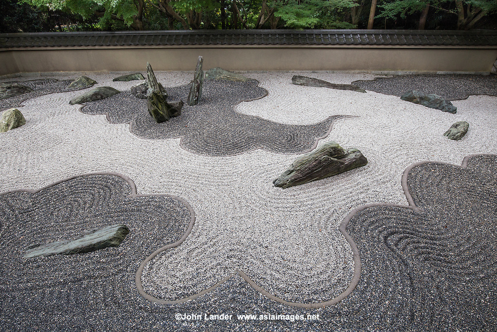 """Ryogin-an was originally the residence of the third abott of Tofuku-ji. The Garden of the Dragon is one of the finest modern karesansui gardens designed by Shigemori Mirei, with stones dramatically placed amidst black and white gravel - each dark area represents a dragon or clouds.  The Eastern garden is the """"Garden of the Inseparable"""", with a simple ginkgo tree standing in the background. This garden uses purple gravel that is not common for zen gardens, and hints at the recency of its design. All three gardens were designed by Shigemori Mirei a modern master landscape gardener who designed other gardens in Tofukuji as well as others in Kyoto and around Japan"""