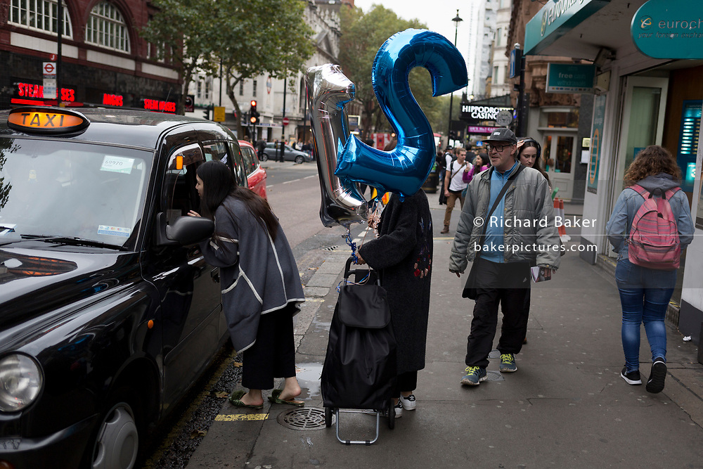 Young women hail a black cab while carrying 21st birthday balloons, on Charing Cross Road, on 19th October 2017, in London, England.