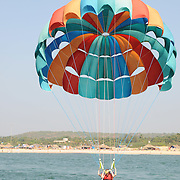 Girl and guy parasaing together on one parachute touching the water surface