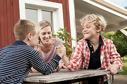 Two young boys arm wrestling mother watching