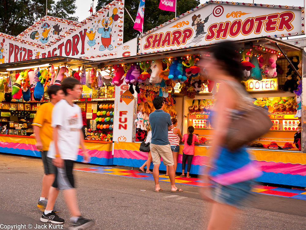 """01 SEPTEMBER 2011 - ST. PAUL, MN:  People walk past the games booths on the midway at the Minnesota State Fair. The Minnesota State Fair is one of the largest state fairs in the United States. It's called """"the Great Minnesota Get Together"""" and includes numerous agricultural exhibits, a vast midway with rides and games, horse shows and rodeos. Nearly two million people a year visit the fair, which is located in St. Paul.  PHOTO BY JACK KURTZ"""