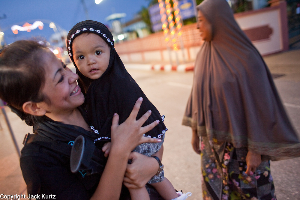 Sept. 29, 2009 -- YARANG, THAILAND: A member of the women's Ranger unit plays with a Muslim baby during a security operation in the night market in Yarang, Thailand, Sept. 29. The 39 women in the 44th Army Ranger Regiment are the only Thai women seeing front line active duty against Moslem insurgents in Thailand's deep south provinces of Pattani, Narathiwat and Yala. All of the other women serving in Thai security services are employed as office and clerical workers. The Ranger women are based at the Ranger camp in the Buddhist village of Baan Trokbon in Sai Buri district of Pattani province. The unit was formed in 2006 after Muslims complained about the way Thai soldiers, all men, treated Muslim women at roadblocks and during security sweeps. The women are frequently called upon to back up Thai regular army units when they are expected to encounter a large number of Muslim women. At least two of the women have been killed by Muslim insurgents. The unit has both Muslim and Buddhist members. Many of the women in the unit joined after either their fathers or husbands were killed by insurgents.  Photo by Jack Kurtz / ZUMA Press