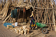 A young girl pushes her wheelbarrow away from a wood stall that supplies building materials and fire timber in the 4 sq km Abu Shouk refugee camp which is (disputedly) home to 38,000 displaced persons and families on the outskirts of the front-line town of Al Fasher (also spelled, Al-Fashir) in north Darfur. The camp has 17 schools, clinics and commercial activity  based around a market, furniture manufacture and variety of cottage industries and a third of families in the camps are headed by women.