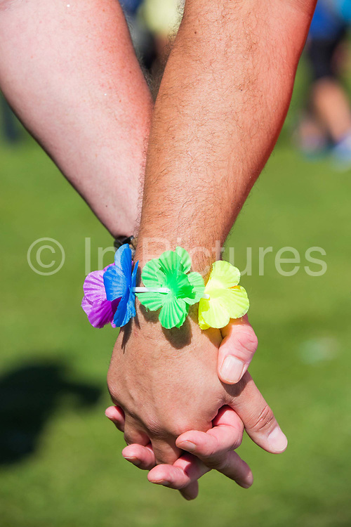 Close up of two men holding hands, one male wearing a rainbow flower bracelet, during the Brighton Pride festival on 6th August 2016 in Brighton in the United Kingdom.