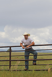 Cowboy standing on a fence on a ranch