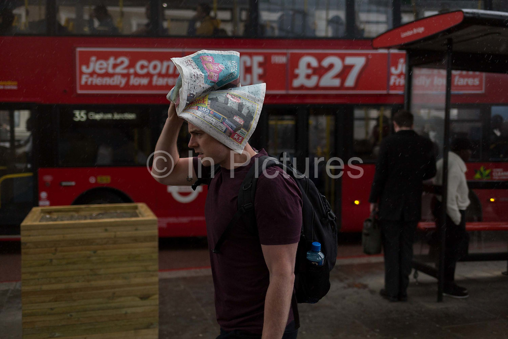 During a spring shower, a male commuter with head covered with a newspaper rushes over London Bridge during the evening rush-hour, from the City southwards to Southwark, on 3rd May, in London, England.