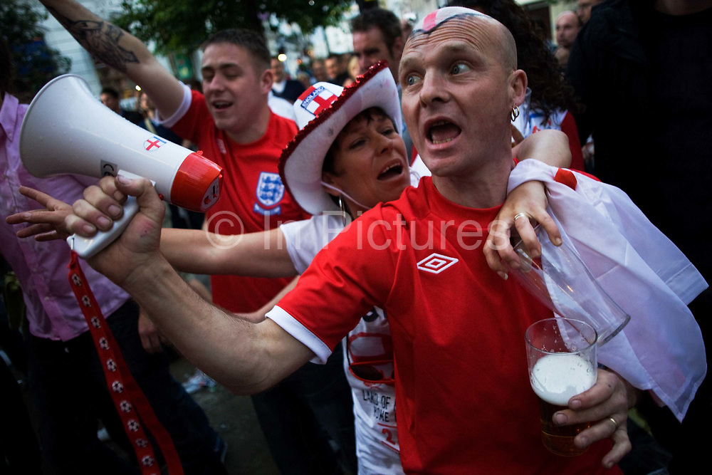 During a televised TV screening in a West End pub, England World Cup football fans have gathered to watch their team's opening match versus USA on TV in London. A bald-headed man is with his drunken partner and he holds a megaphone loudhailer that plays a known football anthem that everyone else sings along to. Dressed in fashionably similar England shirts - complete with the epic Three Lions badge, worn on the team's chests since their 1966 victory - the last national victory. Much alcohol (mostly, lager beer) is consumed and noisy, loutish behaviour can be heard in the capital's streets.