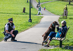 © Licensed to London News Pictures. 15/04/2020. London, UK. A Policeman speaks to a women with her dog on a bench while patrolling Primrose Hill in North London as Ministers decide when and how the lockdown will finish as politicians are warned that the UK could face the worst recession in 300 years. Photo credit: Alex Lentati/LNP