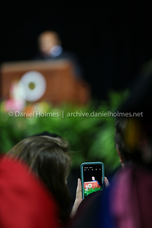 (5/26/19, WORCESTER, MA) A faculty member takes a photo of civil rights icon and U.S. Rep. John Lewis as he delivers the commencement address during the Framingham State University's undergraduate commencement ceremony at the DCU Center in Worcester on Sunday. [Daily News and Wicked Local Photo/Dan Holmes]