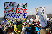 January, 21st, 2017 - Paris, Ile-de-France, France: Capitalism Machismo Assassins placard and Woman as Eiffel Tower Protest banner. Thousands of protesters in Paris join anti-Trump Women's March around the world.
