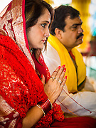 """09 SEPTEMBER 2013 - BANGKOK, THAILAND: A woman prays during Ganesha Chaturthi celebrations at Shiva Temple in Bangkok. Ganesha Chaturthi also known as Vinayaka Chaturthi, is the Hindu festival celebrated on the day of the re-birth of Lord Ganesha, the son of Shiva and Parvati. The festival, also known as Ganeshotsav (""""Festival of Ganesha"""") is observed in the Hindu calendar month of Bhaadrapada. The date usually falls between 19 August and 20 September. The festival lasts for 10 days, ending on Anant Chaturdashi. Ganesha is a widely worshipped Hindu deity and is revered by many Thai Buddhists. Ganesha is widely revered as the remover of obstacles, the patron of arts and sciences and the deva of intellect and wisdom.     PHOTO BY JACK KURTZ"""