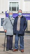 25th February, Cheltenham, England. A portrait of two shoppers wearing masks during the third national lockdown.