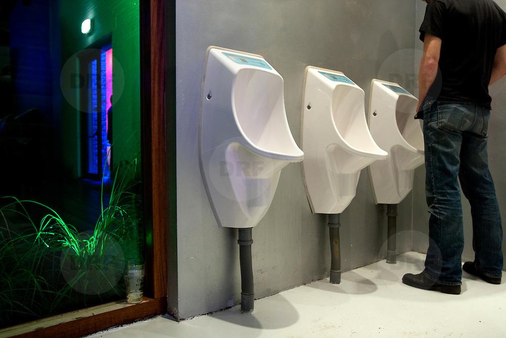 """Nederland Rotterdam 2 september 2008 20080902 Foto: David Rozing.Opening WATT, Werelds eerste Sustainable DanceClub .Bezoeker maakt gebruik van waterloze urinoir. Dit is een van de milieu vriendelijke toepassingen in WATT. Alle urinoirs op het herentoilet zijn waterloos.Hiermee wordt op jaarbasis bijna 1.000 m3 water bespaard. Daarmee kan je 1,5wedstrijdbad vullen. ..VISIE WATT .WATT is het spraakmakende en experimentele """"pop""""podium van Nederlandmet een kwalitatieve horecagelegenheid waar frisse service eninspirerende beleving voorop staan. WATT is city credible en toontaan dat uitgaanscultuur, duurzaamheid en commercie te combinerenzijn in een succesvolle onderneming. WATT is koploper in duurzaamondernemen binnen de branche en blijft innoveren. Water .Spectacular: pee experienceMeestal is het doorspoelen van het toilet een actie waar je niet bijnadenkt. Bij WATT is dit anders. Wanneer je de (spaar)knop van detransparante stortbak indrukt, zie je het gezuiverde regenwater dateerder op het dak is opgevangen (hemelwatersysteem) voor detransparante waterleidingen aan het plafond stromen. Ineens iszichtbaar hoe bijzonder deze kleine dagelijkse luxe eigenlijk is. .besparingen ..o WATT gebruikt een hemelwaterinstallatie: regenwater wordt ophet dak opgevangen en in een ondergrondse tank gezuiverd, .owaarna het wordt gebruikt voor het spoelen van de toiletten.(ca 550.000 liter = ca 80.000 toiletspoelingen per jaar)Alle urinoirs op het herentoilet zijn waterloos.Hiermee wordtop jaarbasis bijna 1.000 m3 water bespaard. Daarmee kan je 1,5wedstrijdbad vullen. ...Op 4 september gaat de eerste duurzame dancing ter wereld open: Club Watt in Rotterdam. Niet alleen wordt er energie bespaard door gebruik te maken van groene stroom en LED-verlichting, maar er wordt ook energie opgewekt. Een ingenieuze dansvloer zet de energie van het dansend publiek om in elektriciteit..Duurzaamheid speelt een sleutelrol in de exploitatie en bedrijfsvoering van WATT. Zo zal de zaal worden uitgerust me"""