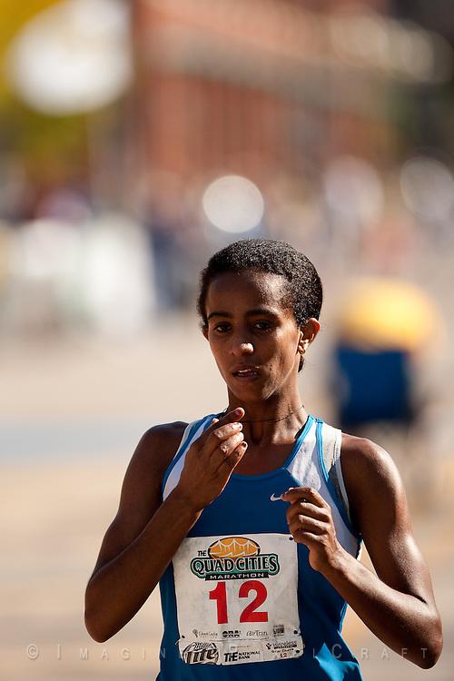 Buzunesh Deba crosses the finish line at the Quad Cities Marathon 2009