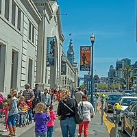 Tourists walk along the Embarcadero in San Francisco, California.