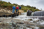 Hywel Thomas, Jaqui Bugden and Gavin Gatehouse checking the inlet at the weir of their new community hydro project.  Ynni Anafon Energy, one of the largest community owned hydro projects in the UK. The site of the Anafon Hydro lies in the Anafon valley in the Carneddau massif which rises immediately south of the village of Abergwyngregyn just inside the northern boundary of the Snowdonia National Park and 4 km west-south-west of Llanfairfechan.