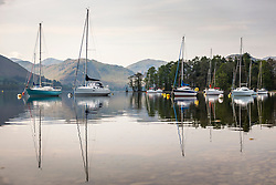© Licensed to London News Pictures. 30/04/2019. Pooley Bridge UK. The moored boats of Fair Field Marina reflect in the calm water of Ullswater lake near Pooley Bridge in Cumbria this morning. Photo credit: Andrew McCaren/LNP