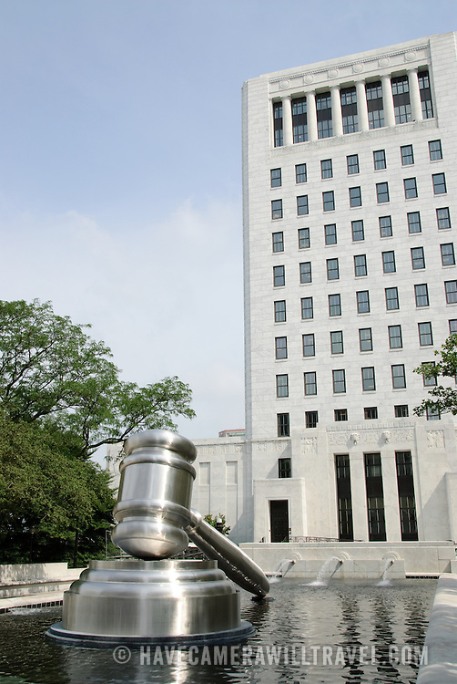 Courthouse building in Columbus Ohio with a large statue of a gavel in the the foreground in the fountain.