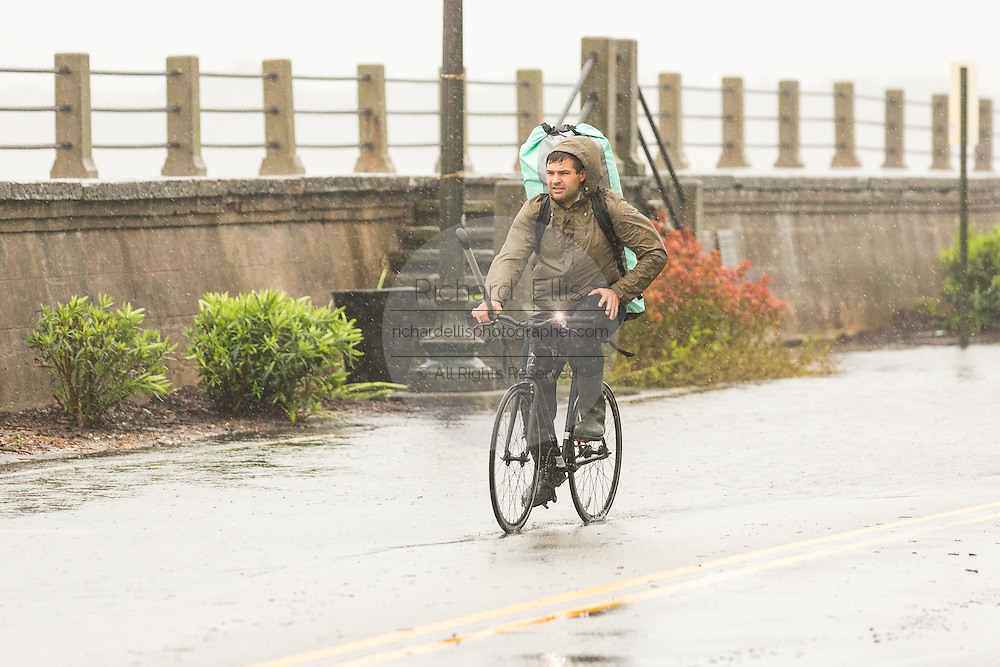 A bicyclist carrying a paddle rides a flooded street along the Battery in the historic district as Hurricane Joaquin brings heavy rain, flooding and strong winds as it passes offshore October 3, 2015 in Charleston, South Carolina.