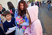 """Oct. 24, 2009 - SCOTTSDALE, AZ: FRANCISCO RAMIREZ, 9, his mother, SALINA SHELTON, and his sister, ANJELICA RAMIREZ, 11, wait in line to get their H1N1 vaccinations at Scottsdale Healthcare's Community Health Services clinic Saturday morning. The first publicly administered H1N1 (""""swine flu"""") vaccinations were given in the Phoenix area Saturday. About 52,000 doses of the vaccine, in both injection and nasal spray form, were available on a first come first served basis, but only to those in so called """"high risk"""" groups: pregnant women, children 6 months to 4 years old, children 5 years to 18 years with underlying health concerns and direct caregivers of infants less than 6 months old. More than 700 people lined up at Scottsdale Health Care, which had 500 doses of the vaccine to administer.     Photo by Jack Kurtz"""