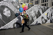 A man carries a bunch of birthday balloons and red flowers past a construction hoarding featuring many faces and expressions.