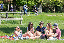 Licensed to London News Pictures. 30/05/2021. London, UK. A group of university students relax in the sun with a cold drink as they enjoy the warm sunshine in Richmond Park, southwest London this afternoon. The Met Office have forecast warm weather and sunshine for the South East and London over the Bank Holiday weekend with temperatures predicted to hit up to 24c for Bank Holiday Monday. Photo credit: Alex Lentati/LNP