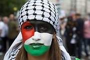 London, UK. Saturday 9th August 2014. Protester with her face painted with the Palestinian flag joins Pro-Palestinian protesters in their tens of thousands march through central London to the American Embassy in protest against the military offensive in Gaza by Israel. British citizens and British Palestinians gathered in huge numbers carrying placards and banners calling to 'Free Palestine' and to 'End the seige on Gaza'.