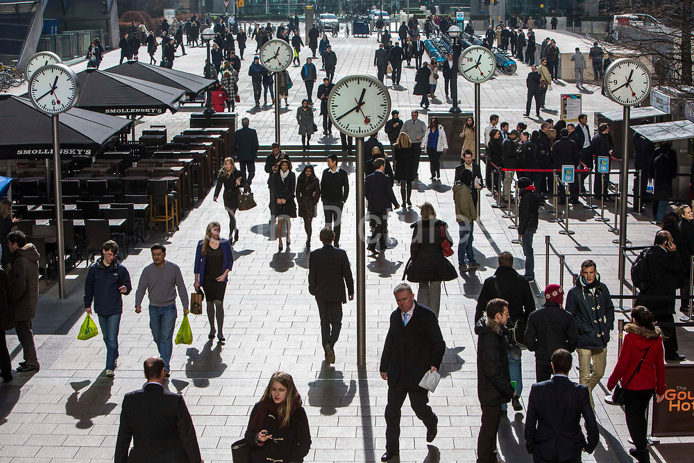 City workers walk under the clocks of Nash Court in Reuters Plaza to commute to work in Canary Wharf financial district London, England, United Kingdom.