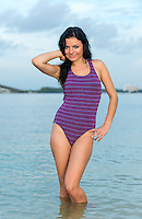 Young woman smiling and very happy early morning in the ocean looking at camera