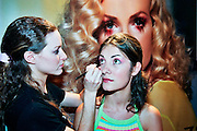 A female make up artist, is aplying makeup to a model
