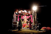 Children are sitting around a Ganesha shrine during the Gampati Festival, dedicated to the famous Indian God with an elephant's head, in the impoverished Oriya Basti colony, Bhopal, Madhya Pradesh, India, near the abandoned Union Carbide (now DOW Chemical) industrial complex.