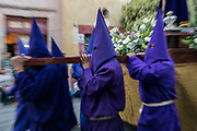 Hooded penitents carry a statue of Jesus during the Procession of Silence through the streets on Good Friday during Holy Week March 30, 2018 in Querétaro, Mexico. The penitents, known as Nazarenes, carry heavy crosses and drag chains in a four hour march to relive the pain and suffering during the passion of Christ.