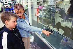 Single mother with young son pointing at shop window display in town centre,